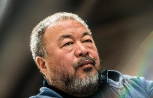 epa05851847 Chinese artist and activist Ai Weiwei poses for the media next to his 70-metre-long giant inflatable installation imitating a life boat in the National Gallery in Prague, Czech Republic, 16 March 2017. The Law of the Journey shows shows a 70-metre-long inflatable boat Installation filled by more than 250 life-size refugees figures  EPA/FILIP SINGER