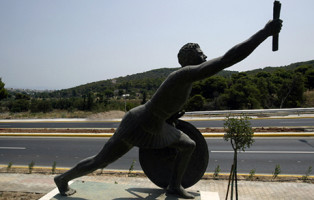 26 Jul 2004, Athens, Greece --- The statue of Pheidippides, the man who ran from Marathon to Athens in 490 B.C to announce Greece's victory against the Persians in one of the most famous battles of ancient times, is placed next to the Marathon route, some 20 kilometres from Athens. The route was plagued by delays and required major renovation of the 42 kilkometre road to Athens. --- Image by © John Kolesidis/Reuters/Corbis