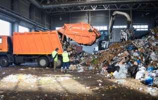 Two workers of recycling plant control process of unloading garbage from garbage truck. Manipulator loads garbage on conveyor for further processing and sorting.