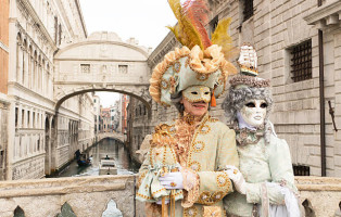 Venice, Italy- February 8, 2015. A couple disguised in Venetian costumes pose in front of Bridge of Sighs during the Venice Carnival days. Shot in St. Mark's Square. The Carnival of Venice is a annual festival held in Venice and is one of the most popular and appreciated carnival in the world.